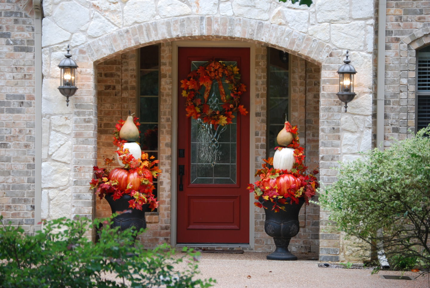 Pumpkin Topiaries sitting in urns on porch area with fall wreath on door
